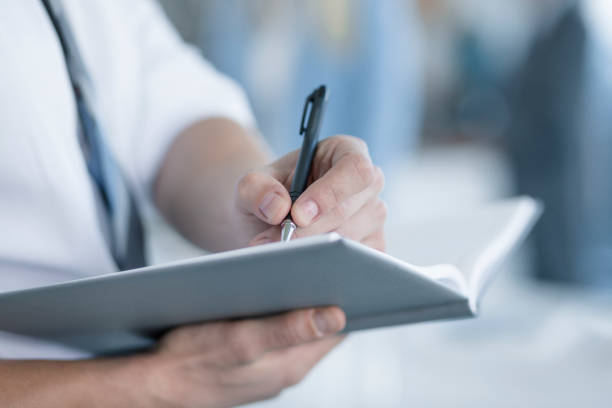Close up of a young business man writing down notes.